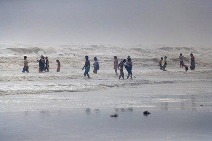 Los visitantes de la playa en Galveston, Texas, juegan en las olas del huracán Hanna el 25 de julio de 2020. REUTERS / Adrees Latif