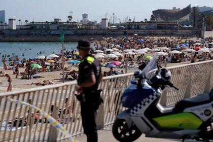 Foto de archivo de un oficial de policía mirando al público disfrutando de un día en la playa de Barcelona.  21 de junio de 2020. REUTERS / Nacho Doce